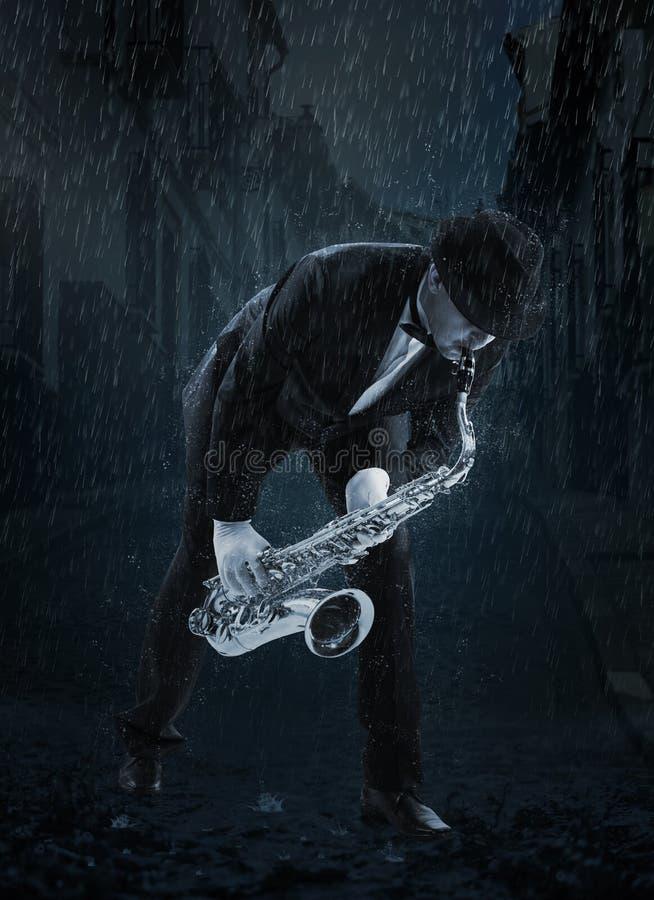 Saxophonist under rain. Saxophonist. Man playing on saxophone under rain stock photos