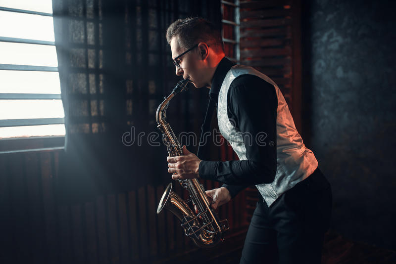 Saxophonist playing jazz melody on saxophone. Male saxophonist playing jazz melody on saxophone against the window stock photos