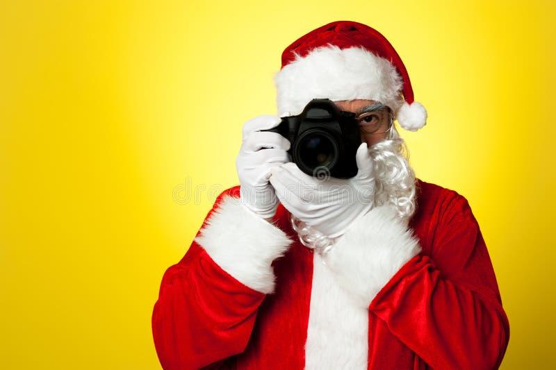Say cheese! Santa capturing a perfect moment royalty free stock photo