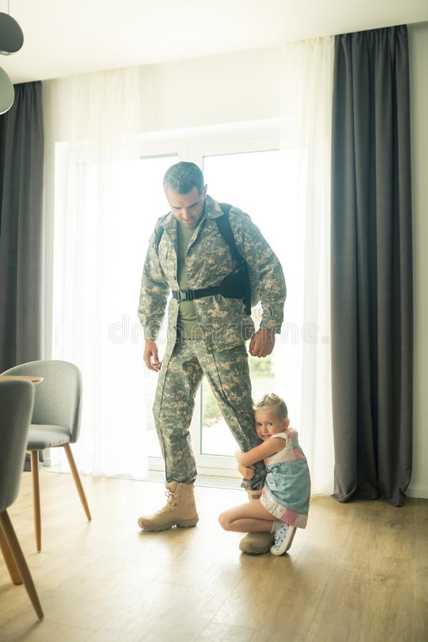 Man leaving home for military service saying goodbye to daughter. Saying goodbye. Man leaving home for military service saying goodbye to little emotional royalty free stock image