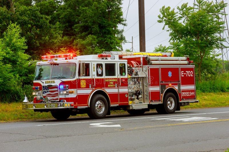 Sayreville NJ EUA - Jujy 02, 2018: O Firetruck que conduz em um azul de piscamento da estrada ilumina um carro danificado acident foto de stock royalty free