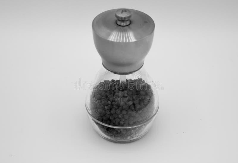 Sazone con pimienta en un echador en un fondo blanco foto de archivo