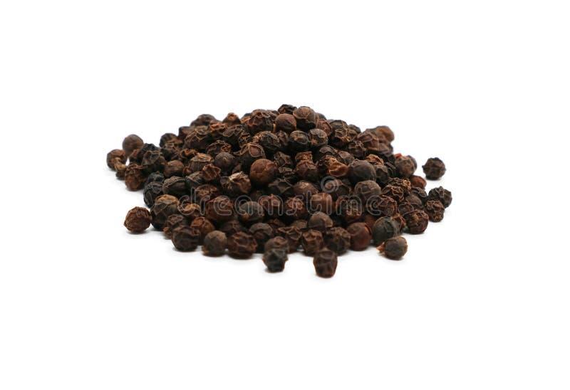 Sazone la pila de aderezo de los guisantes con pimienta negros aislada en blanco foto de archivo