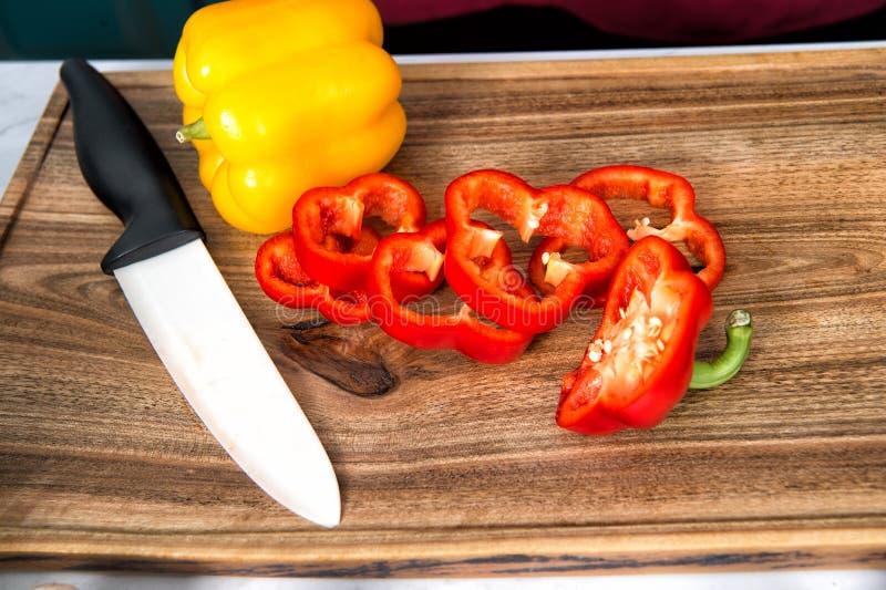 Sazone la verdura de las rebanadas y el cuchillo con pimienta de cerámica en tabla de cortar de madera fotografía de archivo libre de regalías
