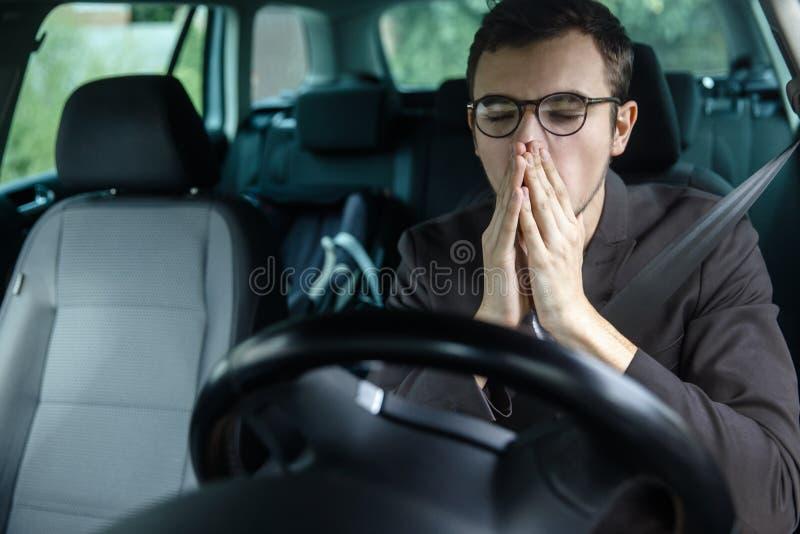 Sbadigli sonnolenti del giovane mentre coprendo la sua bocca di entrambe le mani Concetto di sicurezza stradale immagini stock