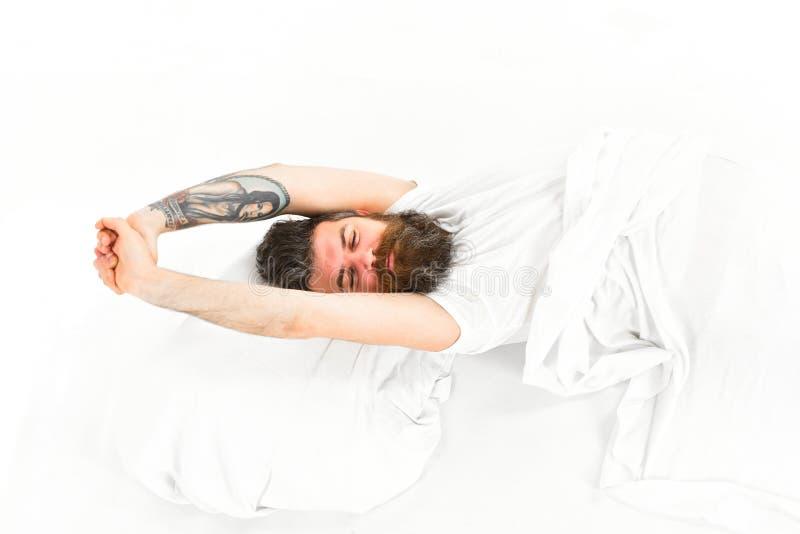 Sbadigliando ed allungando uomo che sveglia a letto fotografie stock