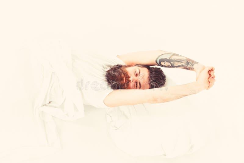 Sbadigliando ed allungando uomo che sveglia a letto immagini stock libere da diritti