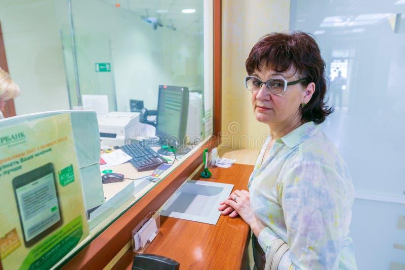 Sberbank della Russia Donna matura che fa una pausa la finestra di una cassa di risparmio fotografie stock libere da diritti