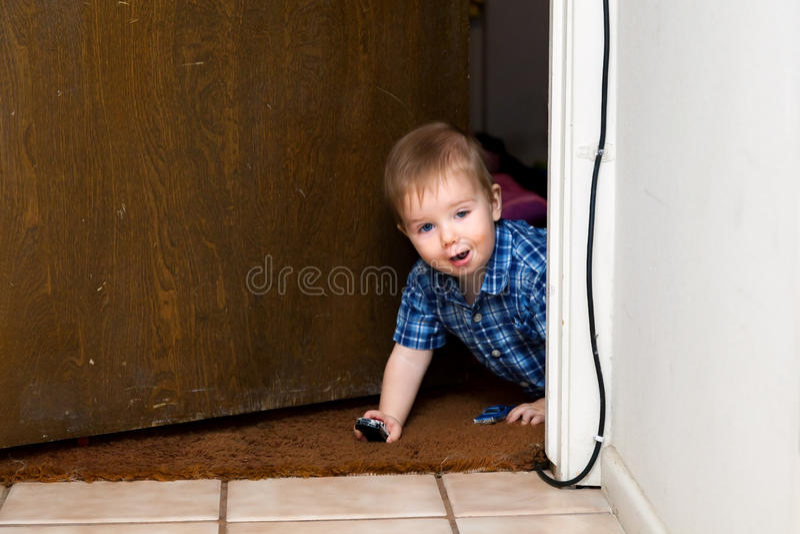 Sbirciate del neonato attraverso una entrata mentre giocando con le automobili fotografia stock libera da diritti