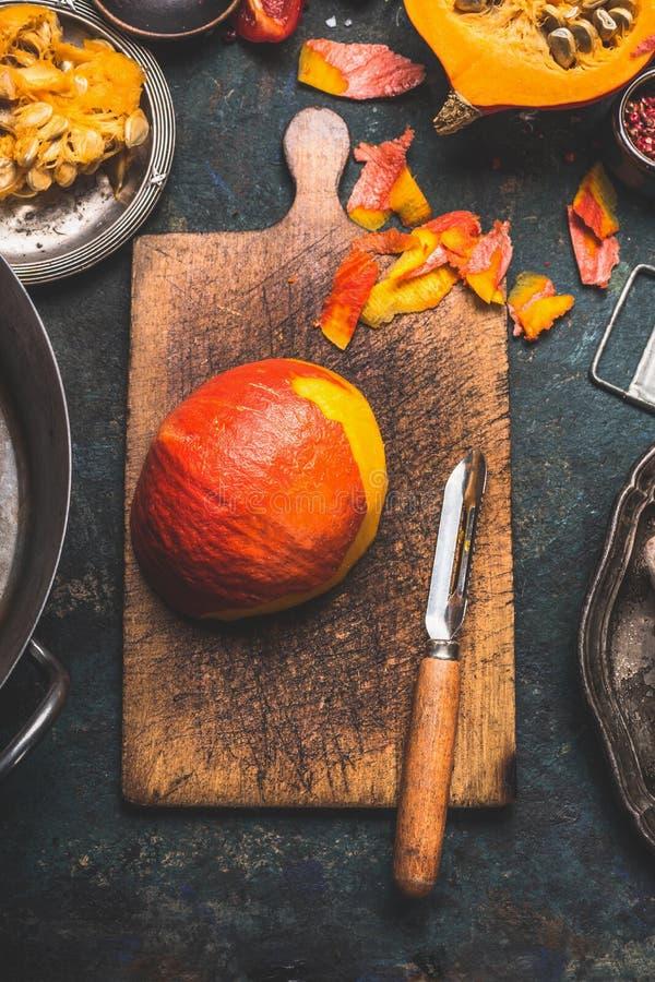 Sbucciatura della zucca sul tagliere rustico con lo sbucciatore delle verdure, fondo di legno scuro immagini stock libere da diritti