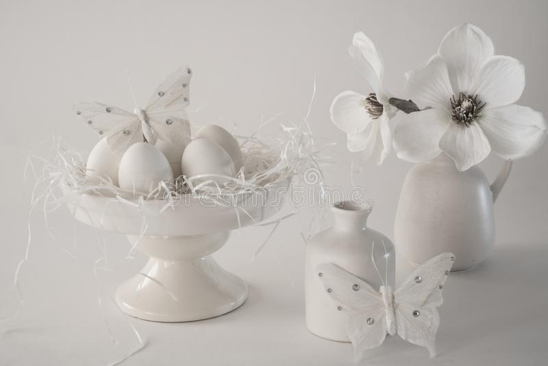 Scène blanche de Pâques de cru, position de gâteau avec des oeufs, vases, fleurs, sur le fond blanc image libre de droits