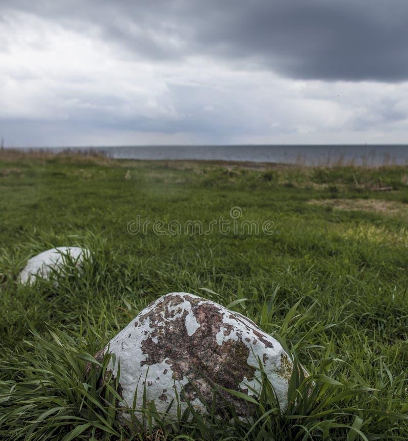 Scène côtière au-dessus d'un pré vers la mer avec de grandes roches photo libre de droits