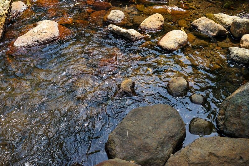 Scène d'écoulement de courant d'eau douce et de hard rock naturel de rivière avec le lichen, la petite vague et le fond de réflex photo stock