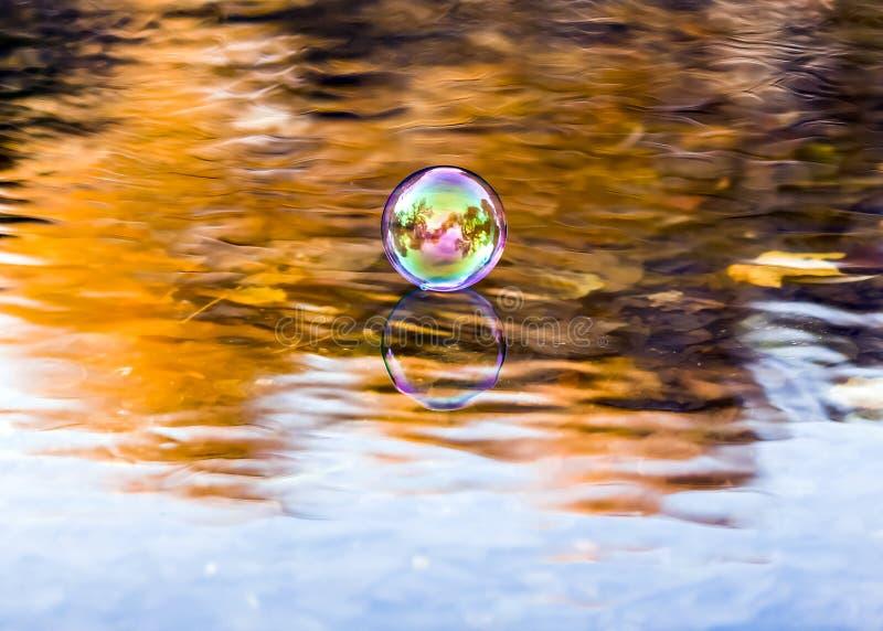 Scène d'automne à une rivière avec l'eau claire et la réflexion d'une bulle de savon photos libres de droits