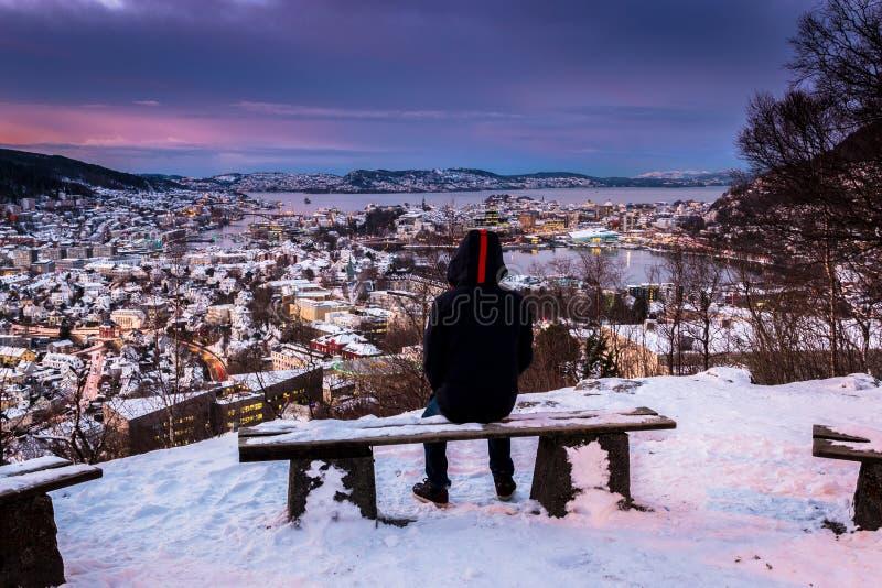 Scène d'hiver avec l'homme solitaire s'asseyant sur le banc de Milou regardant vers le centre de la ville le crépuscule photographie stock