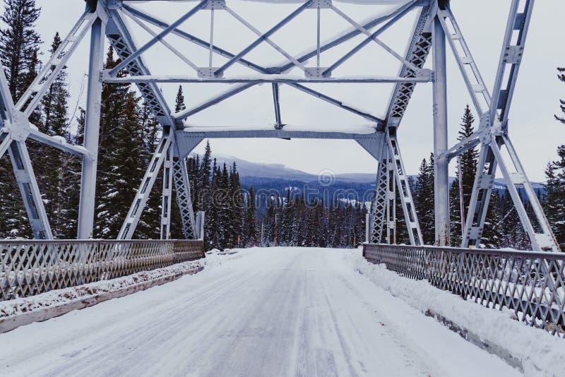 Scène d'hiver d'un pont traversant la rivière d'arc sur la neige couverte, route express glaciale de vallée d'arc en parc nationa images stock