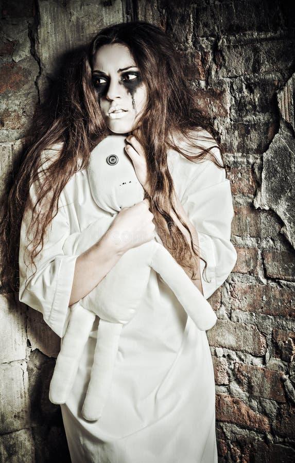 Scène d'horreur : fille folle étrange avec la poupée de chou dans des mains image libre de droits