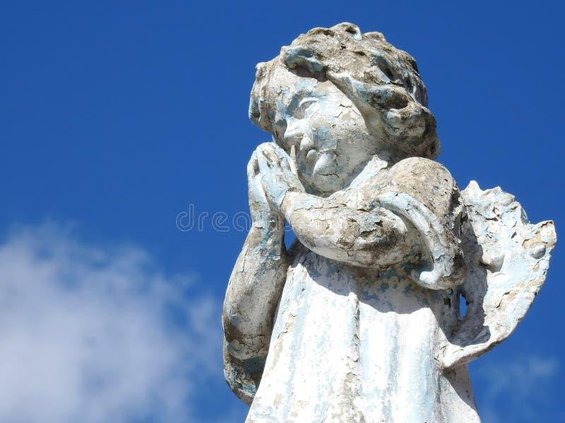 Scène dans un cimetière : le plan rapproché d'une vieille statue en pierre d'un petit ange avec les mains a étreint, priant photo stock