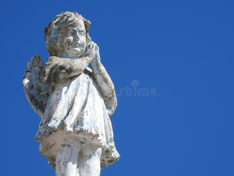 Scène dans un cimetière : le plan rapproché d'une vieille statue en pierre d'un petit ange avec ses mains a étreint, priant photo stock