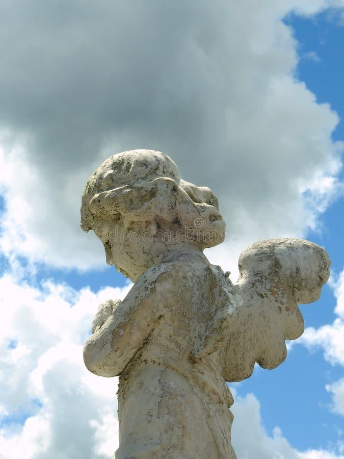 Scène dans un cimetière : plan rapproché d'une vieille statue en pierre d'un petit ange avec des ailes photographie stock libre de droits