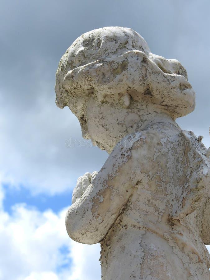 Scène dans un cimetière : plan rapproché d'une vieille statue en pierre d'un petit ange photographie stock libre de droits