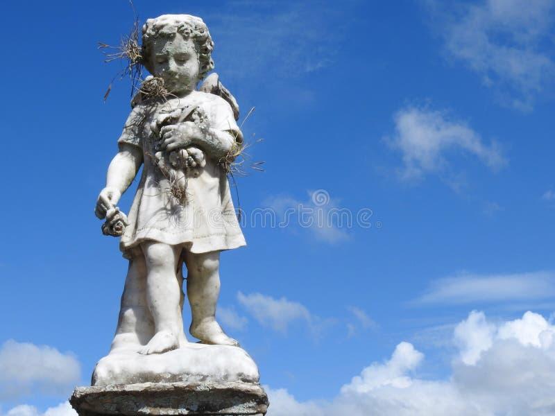 Sc?ne dans un cimeti?re : plan rapproch? d'une vieille statue en pierre d'un petit ange tenant quelques fleurs photos libres de droits