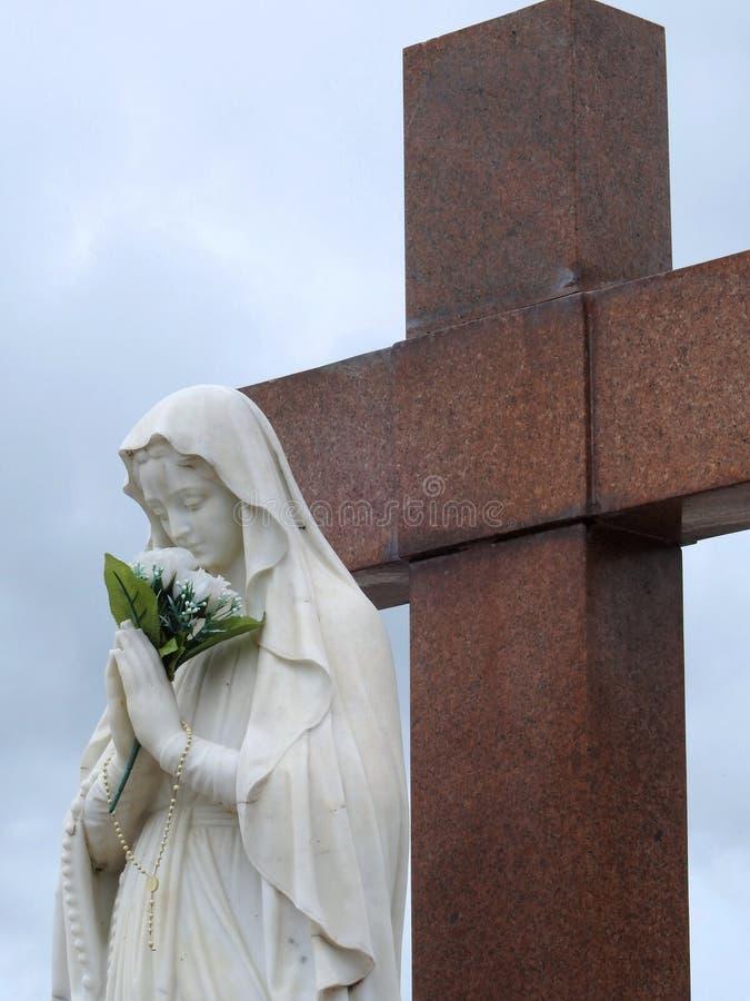 Scène dans un cimetière : statue de Vierge Marie tenant un bouquet des fleurs blanches devant une grande croix de granit image libre de droits
