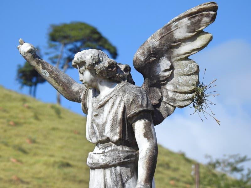 Scène dans un cimetière : une vieille statue en pierre d'un ange photographie stock libre de droits