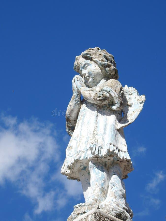 Scène dans un cimetière : une vieille statue en pierre d'un petit ange avec ses mains a étreint, priant photographie stock libre de droits