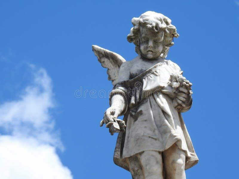Scène dans un cimetière : une vieille statue en pierre d'un petit ange tenant quelques fleurs photo stock