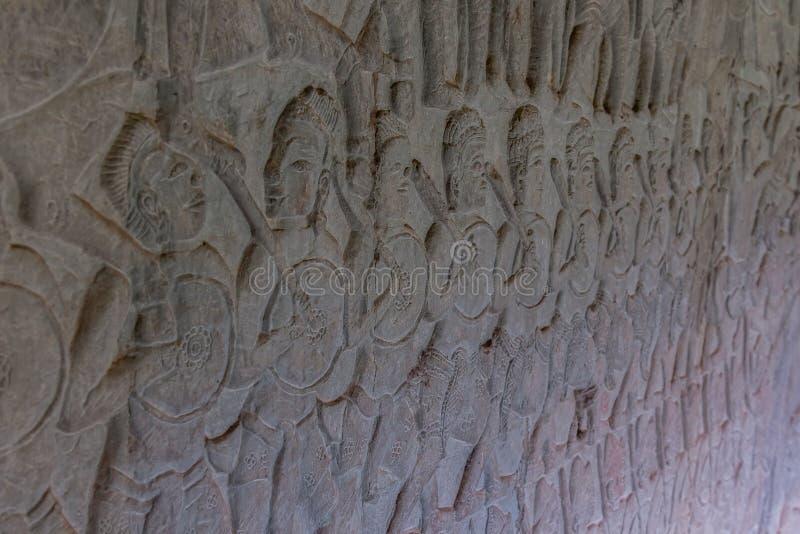 Scène de bataille en pierre découpée dans le temple d'Angkor Vat, parc archéologique, Siem Reap, Cambodge photographie stock libre de droits