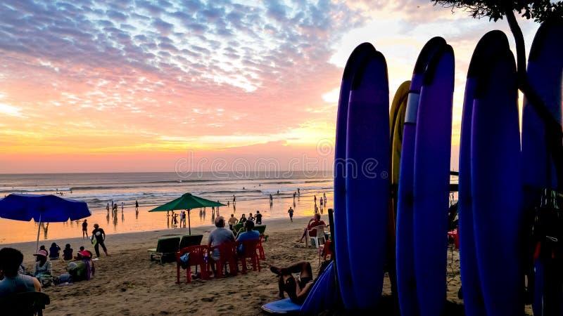 Scène de coucher du soleil avec des planches de surf de position à la plage de kuta, Bali photo libre de droits
