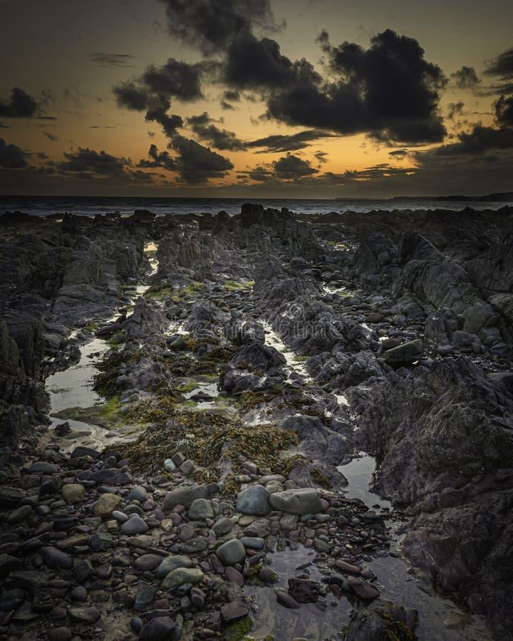 Scène de coucher de soleil sur la belle plage rocheuse de Freshwater West sur la côte de Pembrokeshire, South Wales, Royaume-Uni photos libres de droits