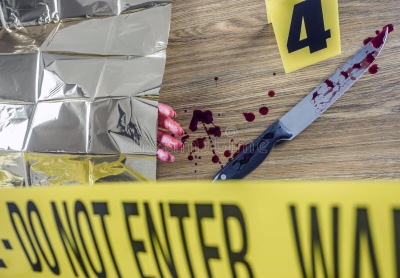 Scène de meurtre pour l'arme de coupe, main sanglante avec un couteau avec le sang photos stock