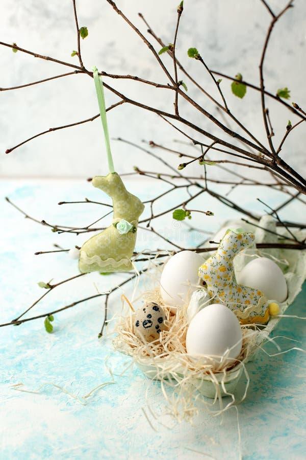 Scène de Pâques avec les branches de verdure de ressort, le lapin et le nid frais des oeufs, fond de fête de printemps image libre de droits