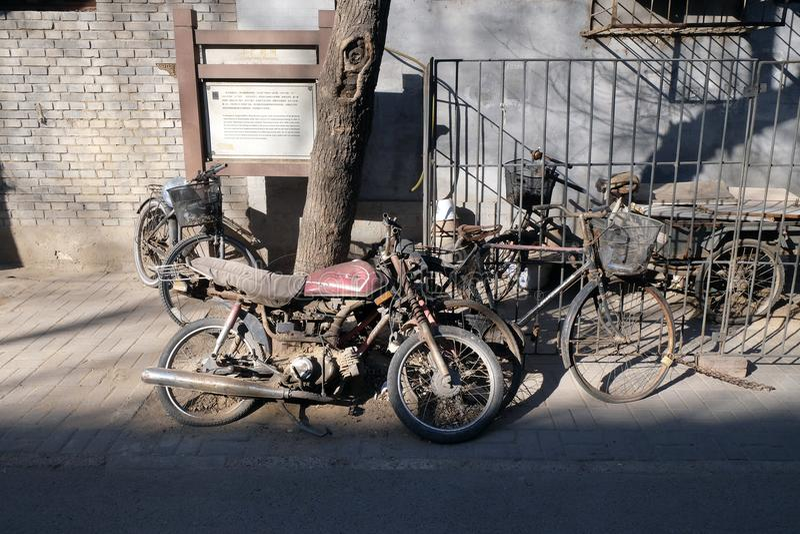 Scène de rue avec la bicyclette et la motocyclette devant une porte de cour dans Pékin images libres de droits