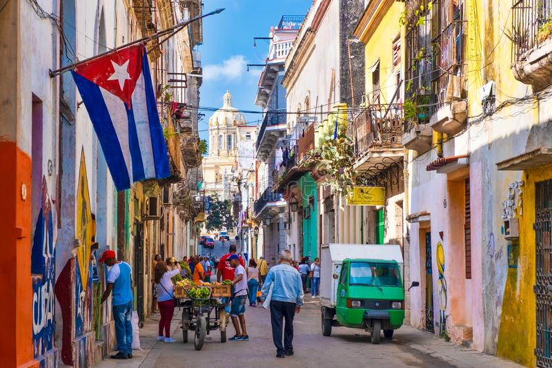 Scène de rue avec le drapeau cubain sur une rue colorée à vieille La Havane photographie stock libre de droits