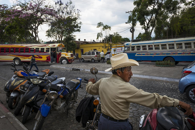 Scène de rue dans la ville de l'Antigua, au Guatemala, avec un homme local dans le premier plan et deux autobus sur le fond, dans photo stock