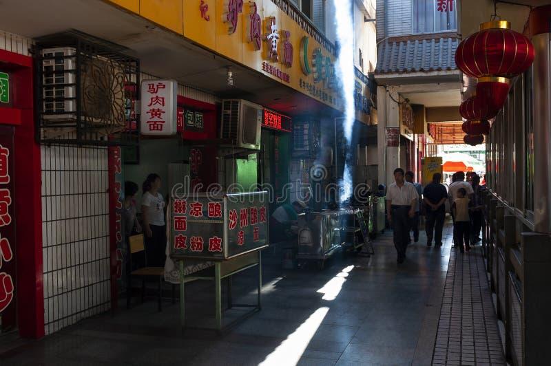 Scène de rue dans la ville de Dunhuang, avec des personnes marchant dans une rue étroite avec des restaurants, en Chine photos libres de droits