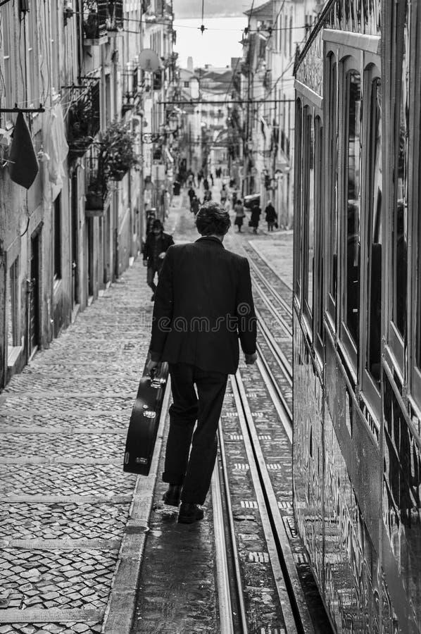 Scène de rue dans la ville de Lisbonne avec un homme portant une valise de guitare descendant la rue de Bica images libres de droits