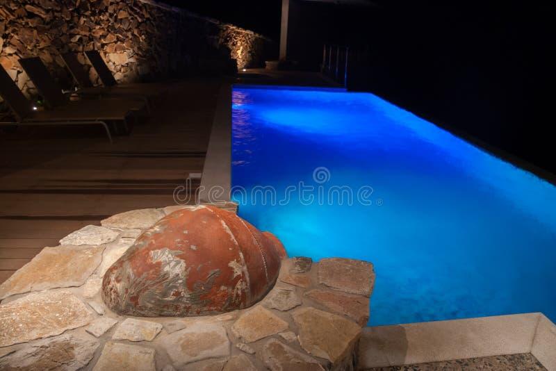 Scène de soirée de piscine d'infini avec une amphore dans le premier plan photo libre de droits