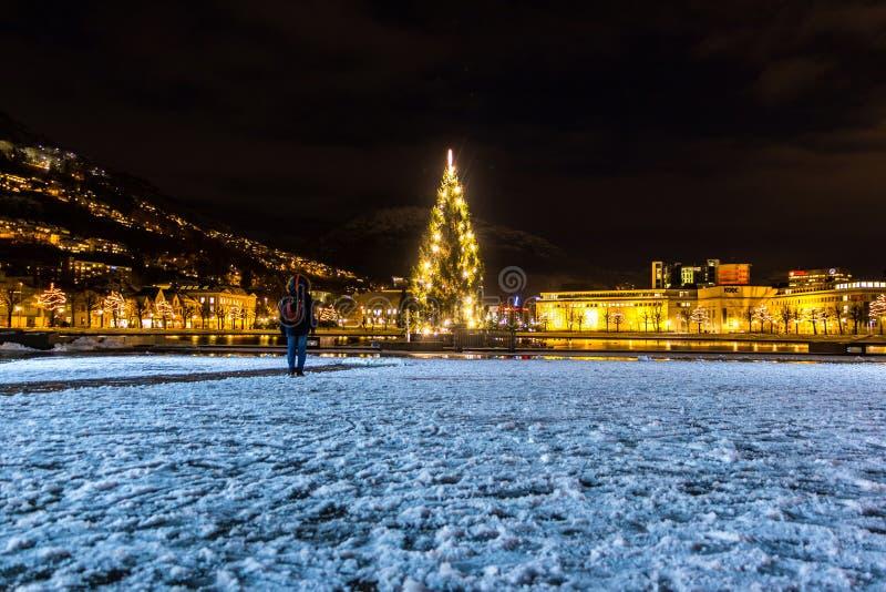Scène de ville d'hiver avec un homme solitaire Standng sur la neige et regarder l'arbre de Noël rougeoyant photo libre de droits