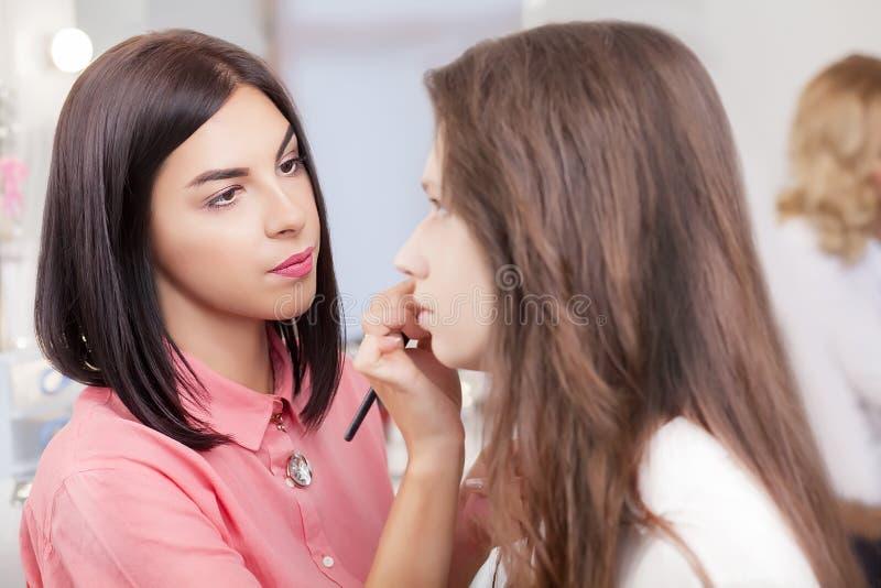 Scène des coulisses : visagiste au travail faisant le maquillage modèle de charme photographie stock libre de droits