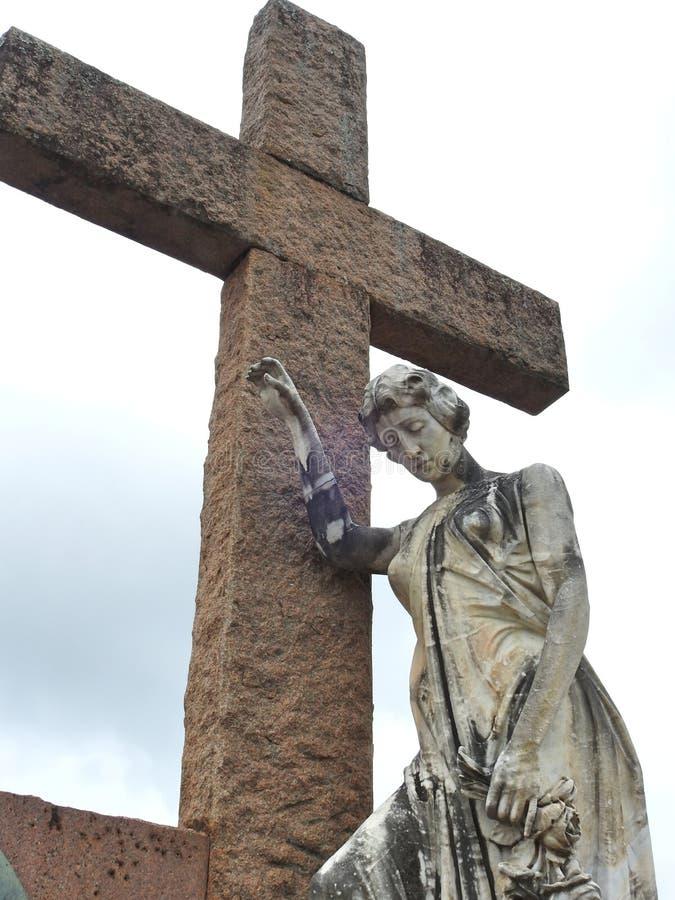 Scène in een kerkhof: standbeeld van een droevige vrouw met haar wapen die tegen een groot steenkruis leunen royalty-vrije stock foto's