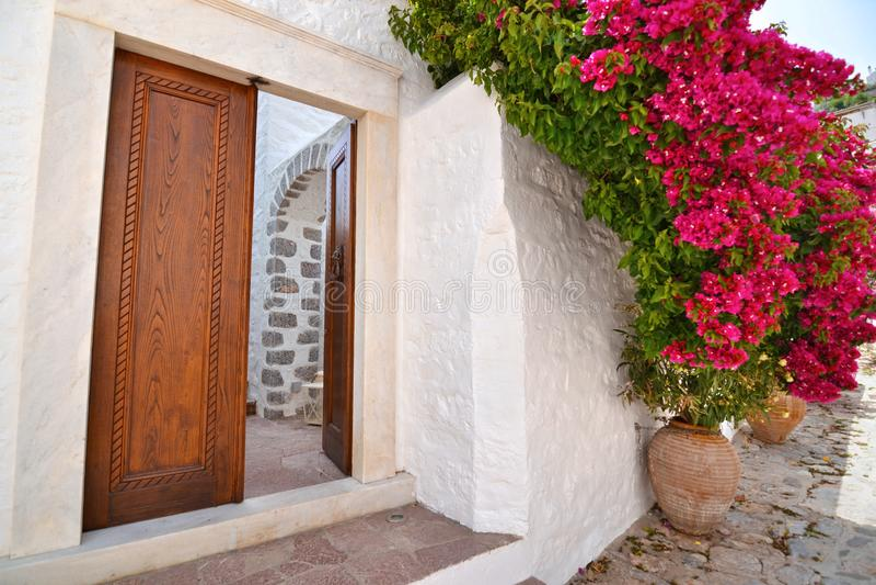 Scène extérieure traditionnelle d'île Grèce d'hydre avec les fleurs de floraison de bouganvillée image stock