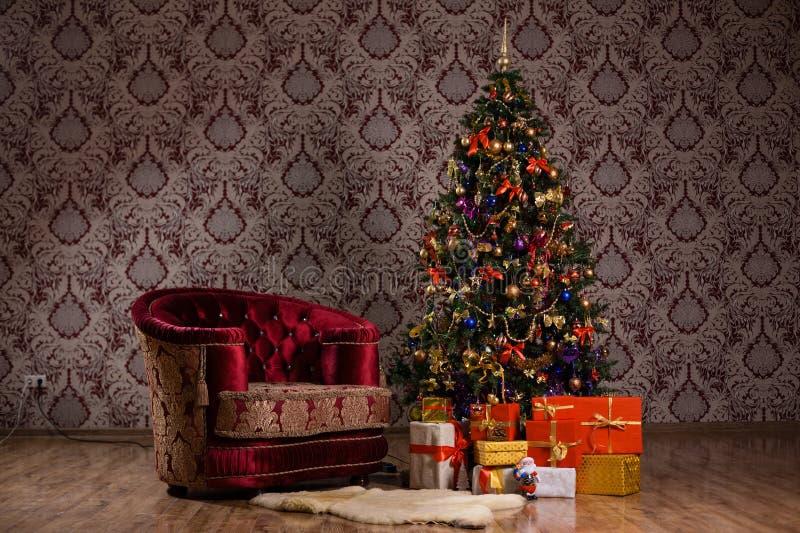 Scène foncée de Noël avec un arbre de Noël décoré, les cadeaux et le fauteuil images libres de droits