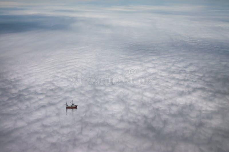 Scène idyllique d'un bateau flottant en nuages images stock
