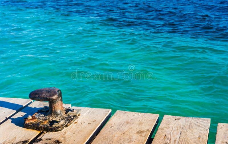 Scène maritime nautique avec la borne sur la jetée en bois et l'eau de mer bleue de turquoise photographie stock libre de droits