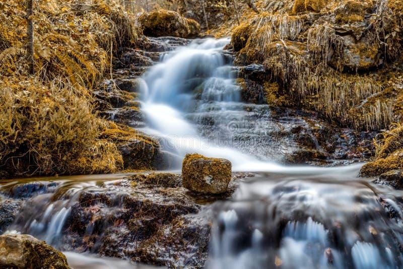 Scène met bergwaterval en rots in voorgrond in de herfst royalty-vrije stock afbeeldingen