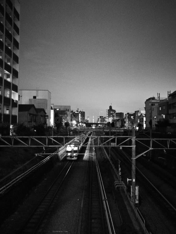 Scène mobile de mouvement de train de nuit hors de centre de la ville dans le noir a photographie stock libre de droits